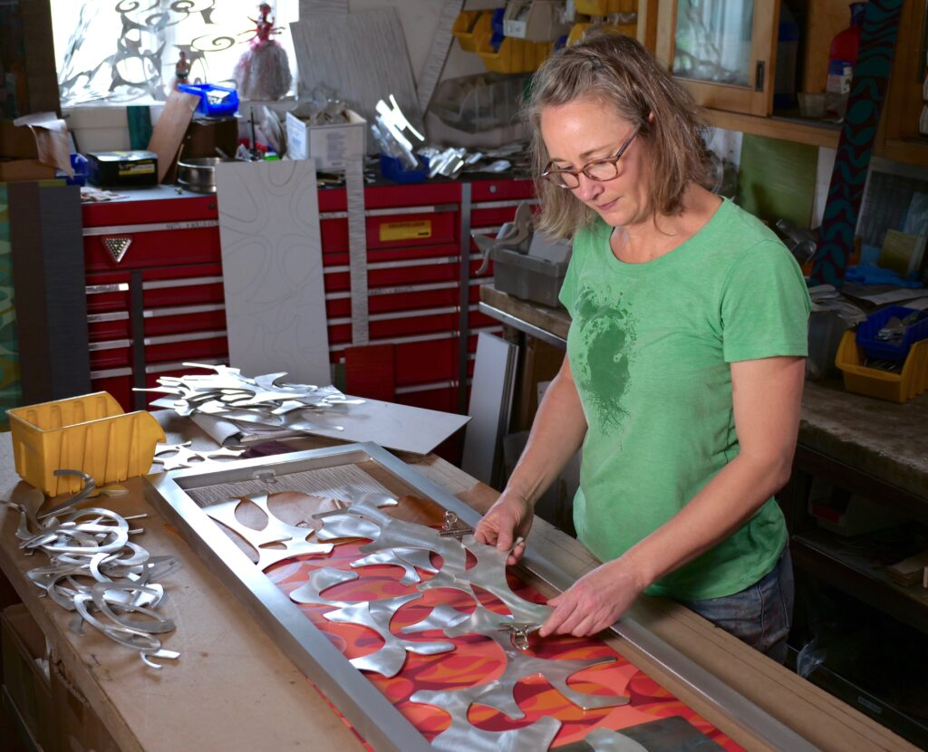 Cherie Haney in her studio assembling a metal wall sculpture