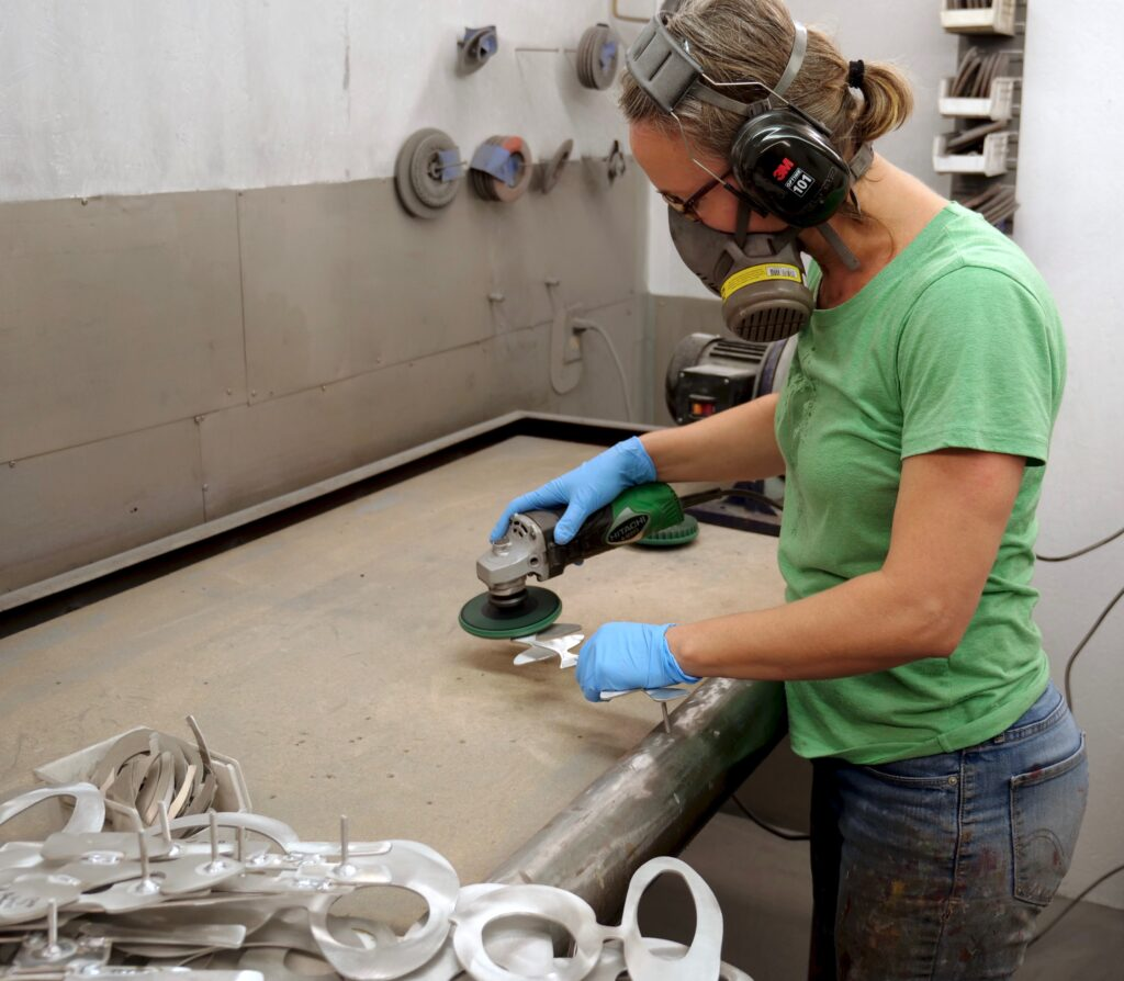Cherie Haney applying a finished surface to welded aluminum pieces
