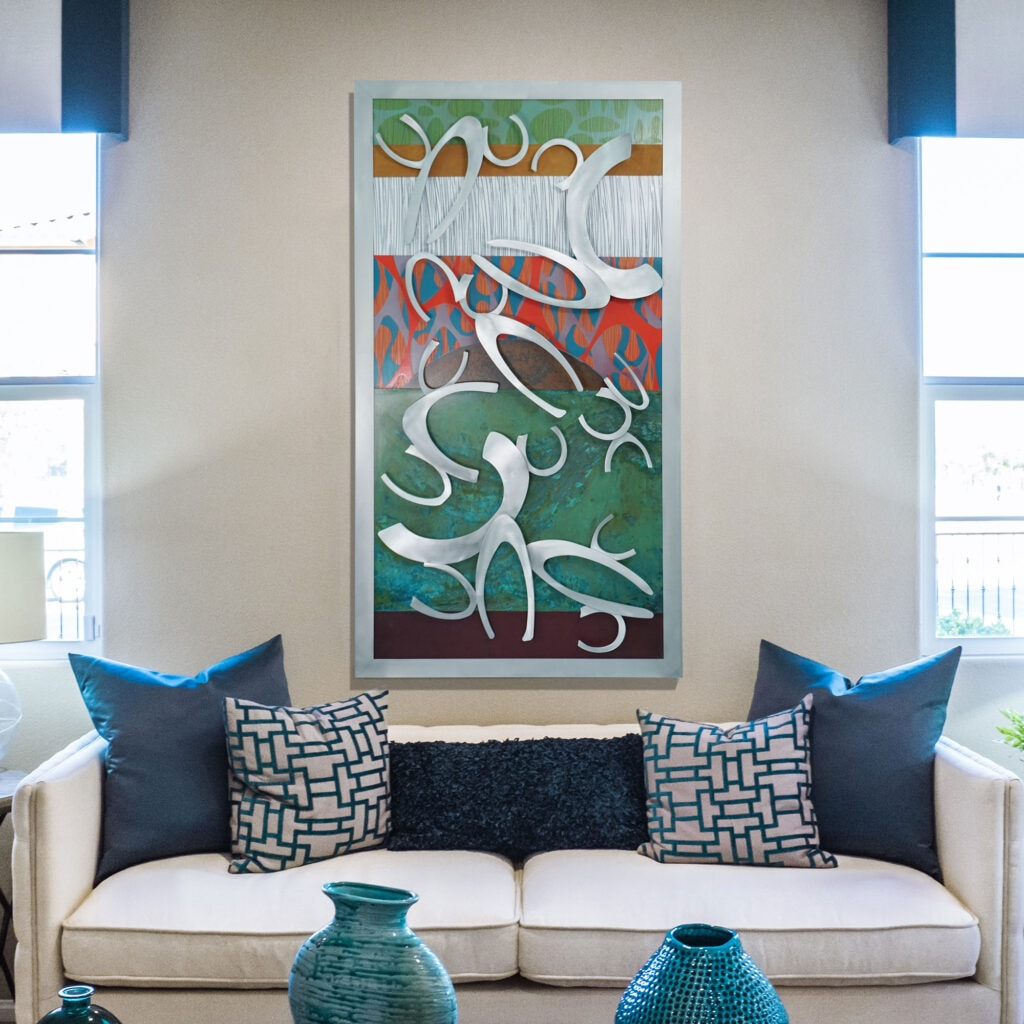 clam pattern with mixed media background hanging behind a couch