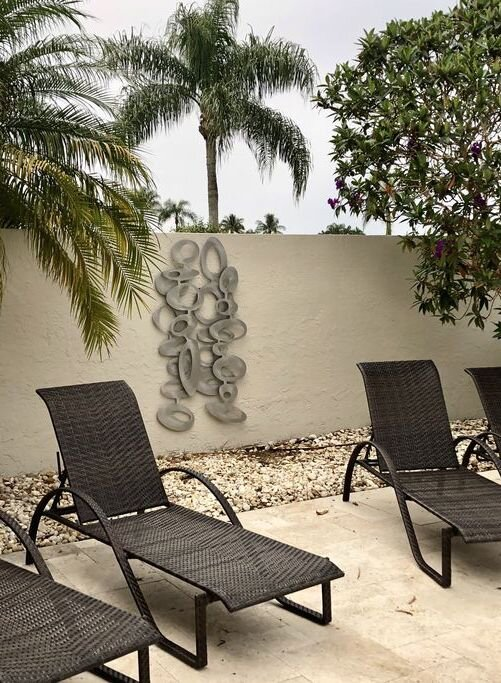freeform olive wall sculpture hanging outdoors on a privacy wall.