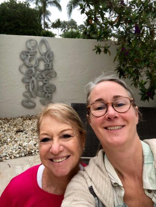 Cherie and her latest client in front of freeform olive wall sculpture